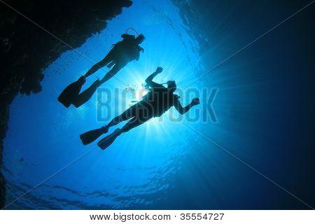 Couple Scuba Diving, silhouettes against sun