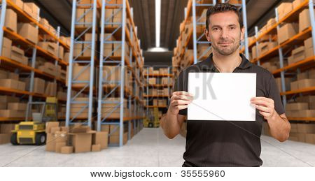 A man holding a blank paper in a distribution warehouse, ideal for inserting your own message