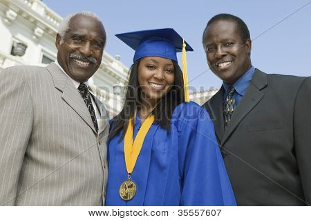 Happy female graduate with father and brother in front of university