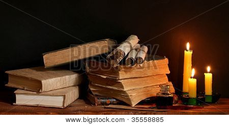 old books, scrolls, ink pen inkwell and candles on wooden table on brown background