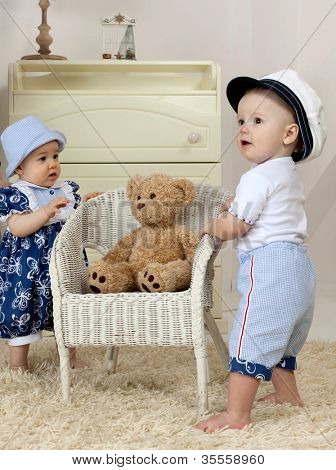 little child baby girl and boy standing near the chair indoors in baby room playing toy teddy bear clothing fashion