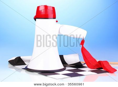 Checkered finish flag and megaphone on blue background