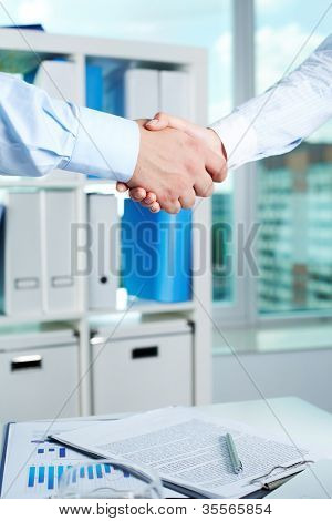 Photo of handshake of business partners after striking deal with signed documents on table