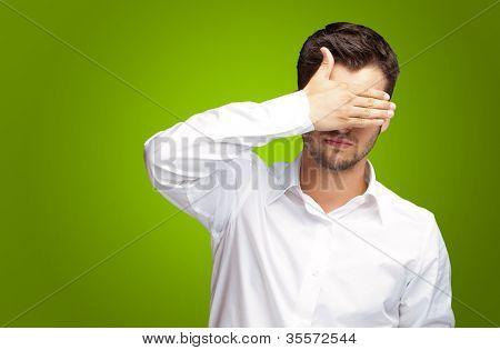 Retrato de um homem de negócios cobrindo os olhos isolados sobre fundo verde
