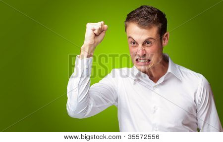 Portrait Of Angry Young Man Clenching His Fist Green Background