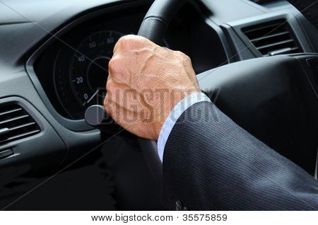 Closeup of a man's hand holding onto the steering wheel of his car. Horizontal format. Car and Driver are unrecognizable.