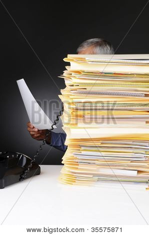 An overworked businessman talking on the telephone hidden behind a large stack of files. Vertical format on a light to dark gray background.