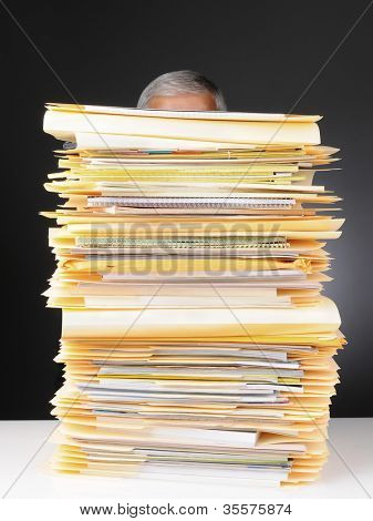 An overworked businessman sitting at his desk hidden behind a large stack of files. Vertical format on a light to dark gray background.