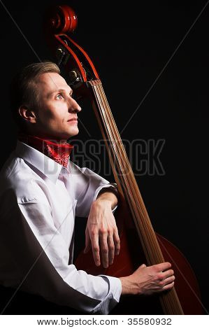 Musician with contrabass. Over black background.
