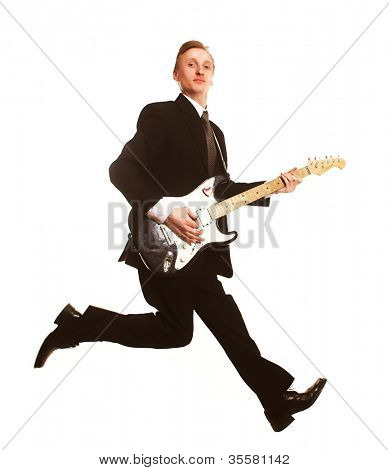 Young businessman jumping with guitar