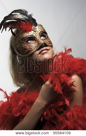Portrait of the  beautiful young woman wearing red carnival mask