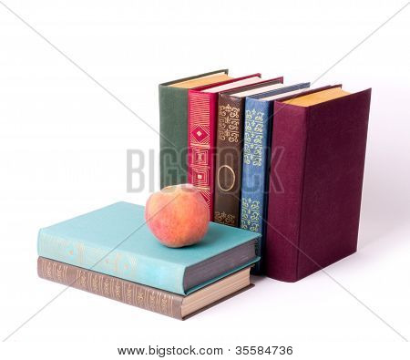 Stack of vintage books with peach isolated on white background