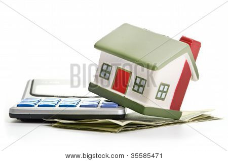 house sitting with a calculator and dollar
