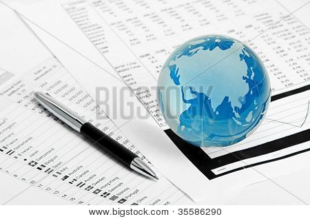 Globo de cristal y lápiz sobre finanzas
