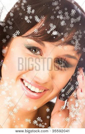 attractive young woman calling by cellular phone and snowflakes