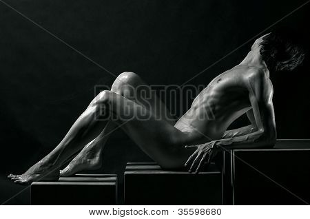Black-and-white studio portrait of a young muscular naked man