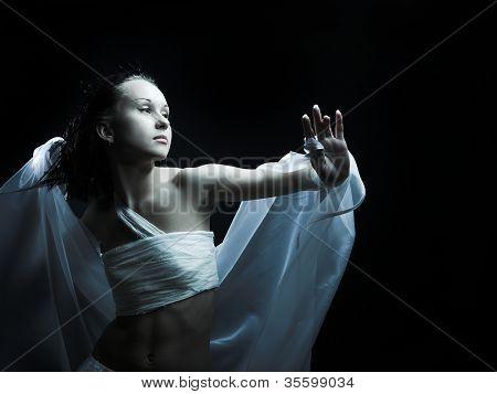 Retrato de una niña en vestiduras blancas, bailando en la penumbra