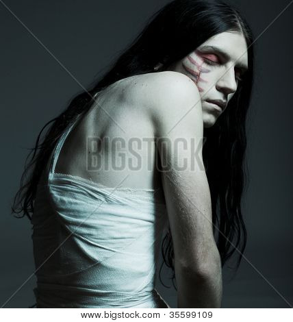 Studio portrait of a young man with paint on his fave and bandage on his body