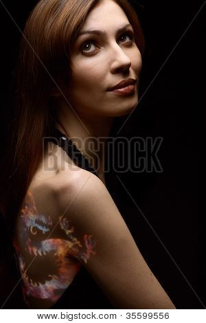Studio portrait of a young beautiful girl with paint on her body