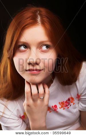 Close-up studio portrait of a read-haired beautiful girl isolated on black background