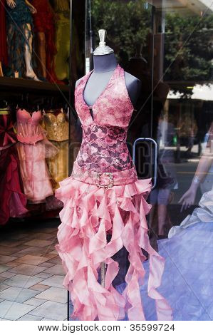 Close-up shot of the store window with a mannequin dressed in fashionable gown