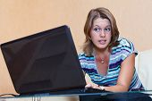 Young Woman Playing In Games On Laptop. Girl Sits In Domestic Room Interior poster