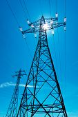 stock photo of utility pole  - the utility pole of a high voltage line with the sun and blue sky - JPG