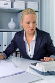 image of depreciation  - an accountant at work in the office with calculator - JPG