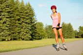 image of inline skating  - Roller skating girl in park rollerblading on inline skates - JPG
