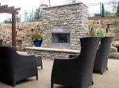 image of log fence  - An outdoor fireplace on the back patio with chairs great for entertaining and relaxation - JPG