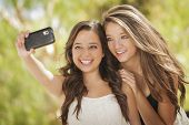 stock photo of two women taking cell phone  - Two Attractive Mixed Race Girlfriends Taking Self Portrait with Their Phone Camera Outdoors - JPG