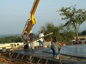 Four Concrete Laborers  Carrying Board