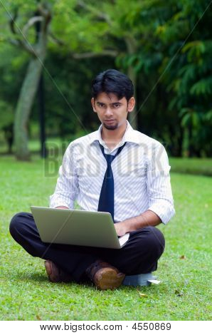 Man Working On Laptop In The Park