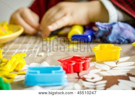 Closeup de moldes de plastilina y las manos del niño en el fondo