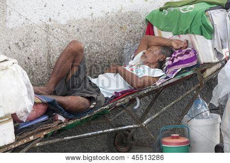 Bangkok, Thailand-sept 25Th: A Homeless Man Sleeps Amongst His Possessions On Septtember 25Th 2012.