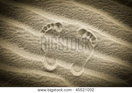 Two Footprints In Sand On The Desert Beach