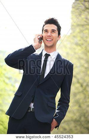 Happy young business man on mobile phone while walking in the city