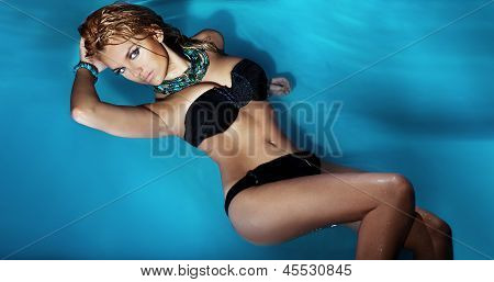 Attractive Blond Girl Lying In Swimming Pool.