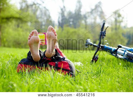 Cyclist On A Halt Reads Lying In Fresh Green Grass Barefoot