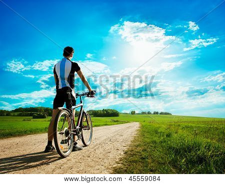 Man with a Bike on Beautiful Nature Background