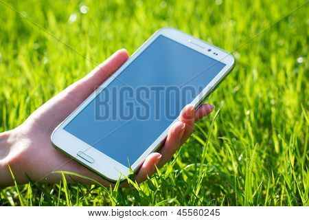 Woman Hand Holding Smart Phone on Green Background