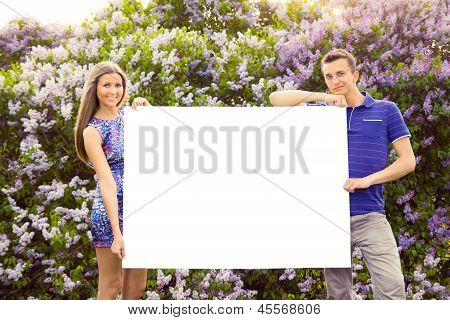 Young couple holding blank poster