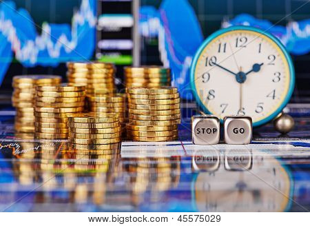 Stacks Of Golden Coins, Clock, Dices Cubes With The Words Stop Go. The Financial Chart As Background