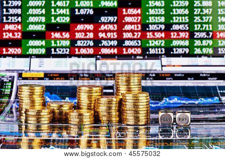 Dices Cubes With The Words Sell Buy, Columns Of Golden Coins And Financial Charts As Background. Sel
