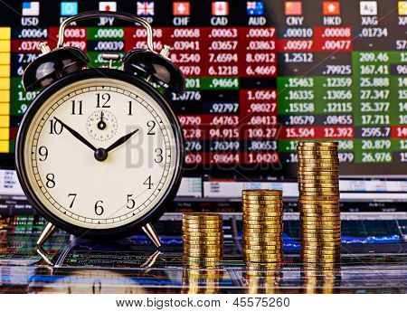 Three Uptrend Stacks Of Golden Coins, Clock And Financial Chart As Background. Selective Focus.
