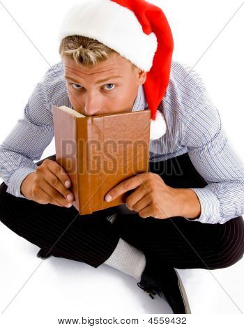 Sitting Man With Book And Christmas Hat