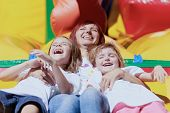 stock photo of laugh out loud  - Mom and her daughters laughing out loud laying on a bouncing castle in a bright summer day outdoors - JPG