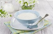 stock photo of porridge  - Rice porridge with milk in a blue bowl on the table - JPG