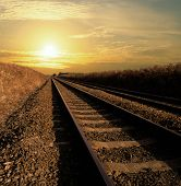 stock photo of train track  - Rail track going into infinity with the sun setting - JPG