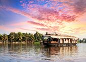 stock photo of houseboats  - House boat in backwaters near palms at dramatic sunset sky in alappuzha Kerala India - JPG